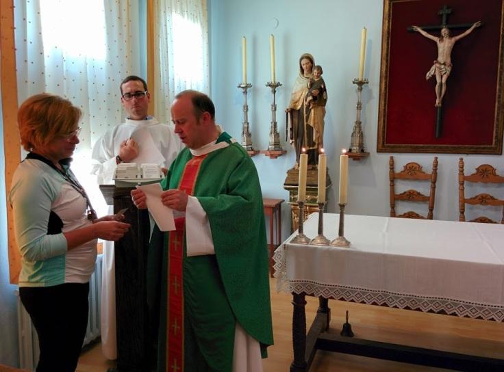 A priest blesses pilgrims in Estella